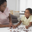 Mother and daughter playing with puzzle — Stock Photo #52072895