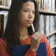 Mixed race woman thinking in library — Stock Photo #52073325