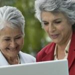 Senior Hispanic women looking at laptop — Stock Photo #52073431