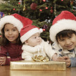Hispanic siblings wearing Santa Claus hats — Stock Photo #52074109