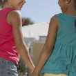 Mixed Race sisters holding hands — Stock Photo #52074247
