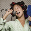 Asian woman in curlers singing — Stock Photo #52074297
