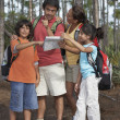 Hispanic family looking at map in woods — Stock Photo #52075045