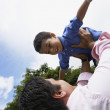 Hispanic father holding son in air — Stock Photo #52075469
