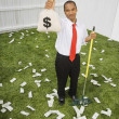 Mixed Race businessman raking up money — Stock Photo #52075487
