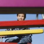 Hispanic boy sitting on seesaw — Stock Photo #52075833