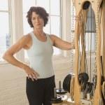 Senior woman standing next to exercise equipment — Foto Stock #52076211