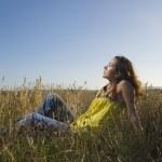 Hispanic woman sitting in field — Stock Photo #52076611