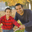 Hispanic father helping son ride bicycle — Stock Photo #52077005