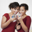 African twin sisters looking at snow globes — Stock Photo #52077813