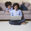 African twin sisters looking at laptop — Foto Stock #52077853