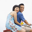 Asian couple sitting on motor scooter — Stock Photo #52078229