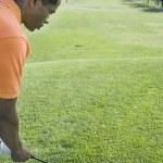 African man swinging golf club — Stock Photo #52079213
