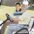 Asian father and adult son in golf cart — Stock Photo #52079241