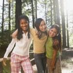 Multi-ethnic girls hugging in woods — Stock Photo #52079937