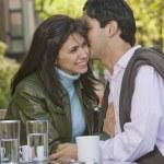 Hispanic man telling secret to girlfriend — Stock Photo #52079959