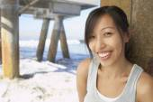 Asian woman smiling near pier at beach — Stock Photo
