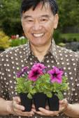 Senior Asian man holding potted plants — Photo