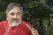 Hispanic man drinking from hose — Stock Photo
