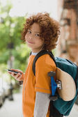 Mixed Race boy listening to mp3 player — Stock Photo