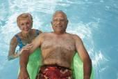 Multi-ethnic senior couple in swimming pool — Stock Photo