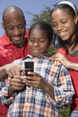 African family looking at cell phone — Stock Photo