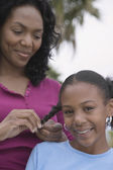 African mother braiding daughter's hair — Stockfoto