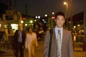 Asian businessman outdoors at night — Stock Photo