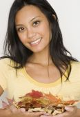 Pacific Islander woman holding autumn leaves — Stock Photo