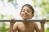 Hispanic boy leaning chin on bar — Stock Photo