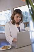 Hispanic woman typing on laptop — Stock Photo