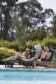 Couple relaxing next to swimming pool — Stock Photo