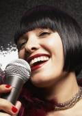 Glamorous woman singing — Stock Photo