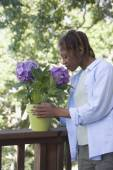 African American woman smelling flowers — Stock Photo