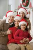 Hispanic family wearing Santa Claus hats — Stock Photo
