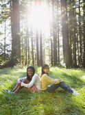 Multi-ethnic girls sitting in woods — Stock Photo