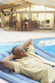 African man laying in hammock at poolside — Stock Photo