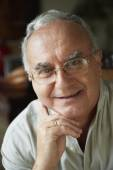 Senior Hispanic man leaning chin on hand — Stock Photo