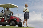 Senior African American couple with golf cart — Stockfoto