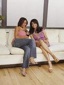 Multi-ethnic women sitting on sofa — Stock Photo