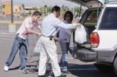 Hispanic family loading groceries into car — Stock Photo