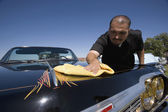 Hispanic man buffing show car — Stock Photo