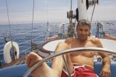 Man steering sailboat with foot — Stock Photo