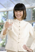Asian woman holding glass of water — Stock Photo