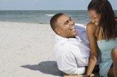 Afrikanska par skrattar åt stranden — Stockfoto