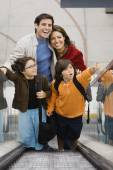 Hispanic family on escalator — Stock Photo