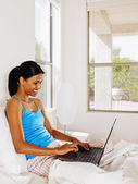 Indian woman typing on laptop — Stock Photo
