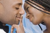 African bride touching groom's lips — Stock Photo