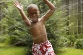 African American boy playing in sprinkler — Stock Photo