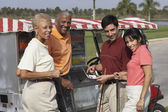Multi-ethnic couples at food stand on golf course — Stock Photo